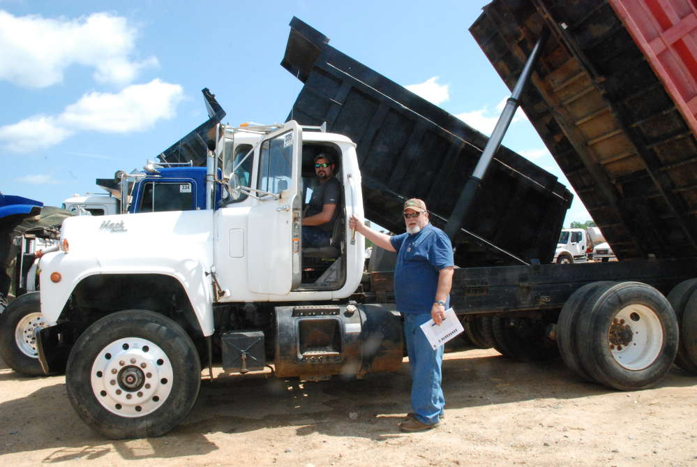 George Pittman (L) and Myles Mayo, both of Richton, Miss., take a seat in a Mack dump truck that was in the May 13 to 14 auction held in Brooklyn, Miss.