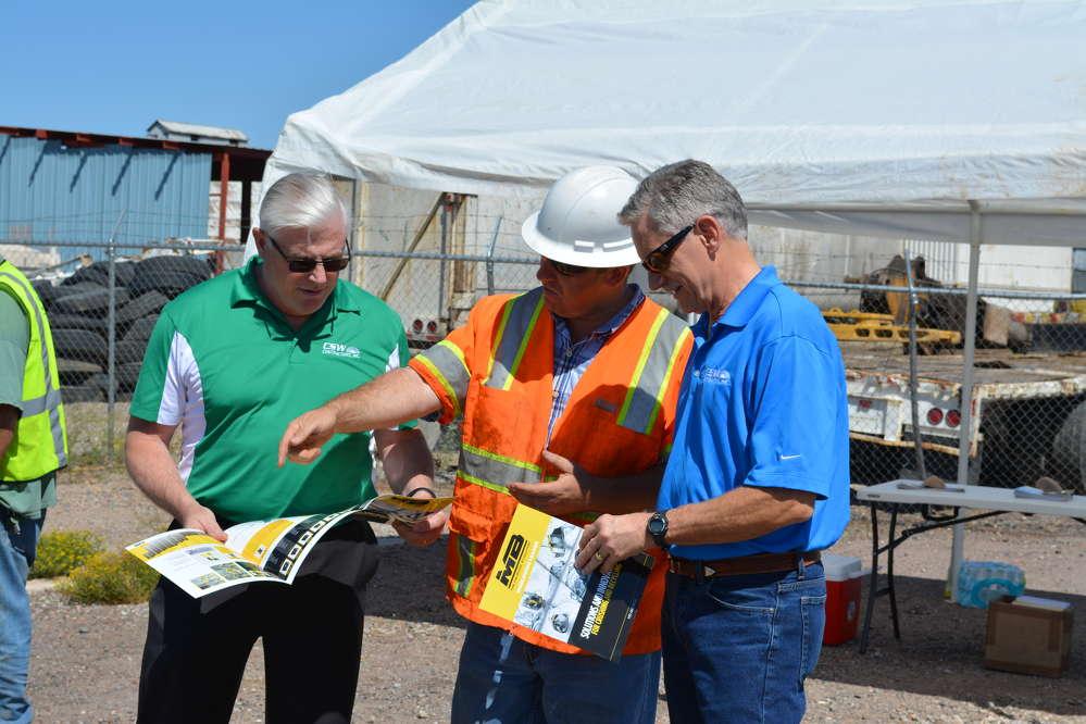 Blair Larson (L), chief estimator of CSW Contractors, Phoenix, Ariz., and Mike Claflin (R), CSW's senior estimator, discuss the MB Crusher with Dominic McNamara.