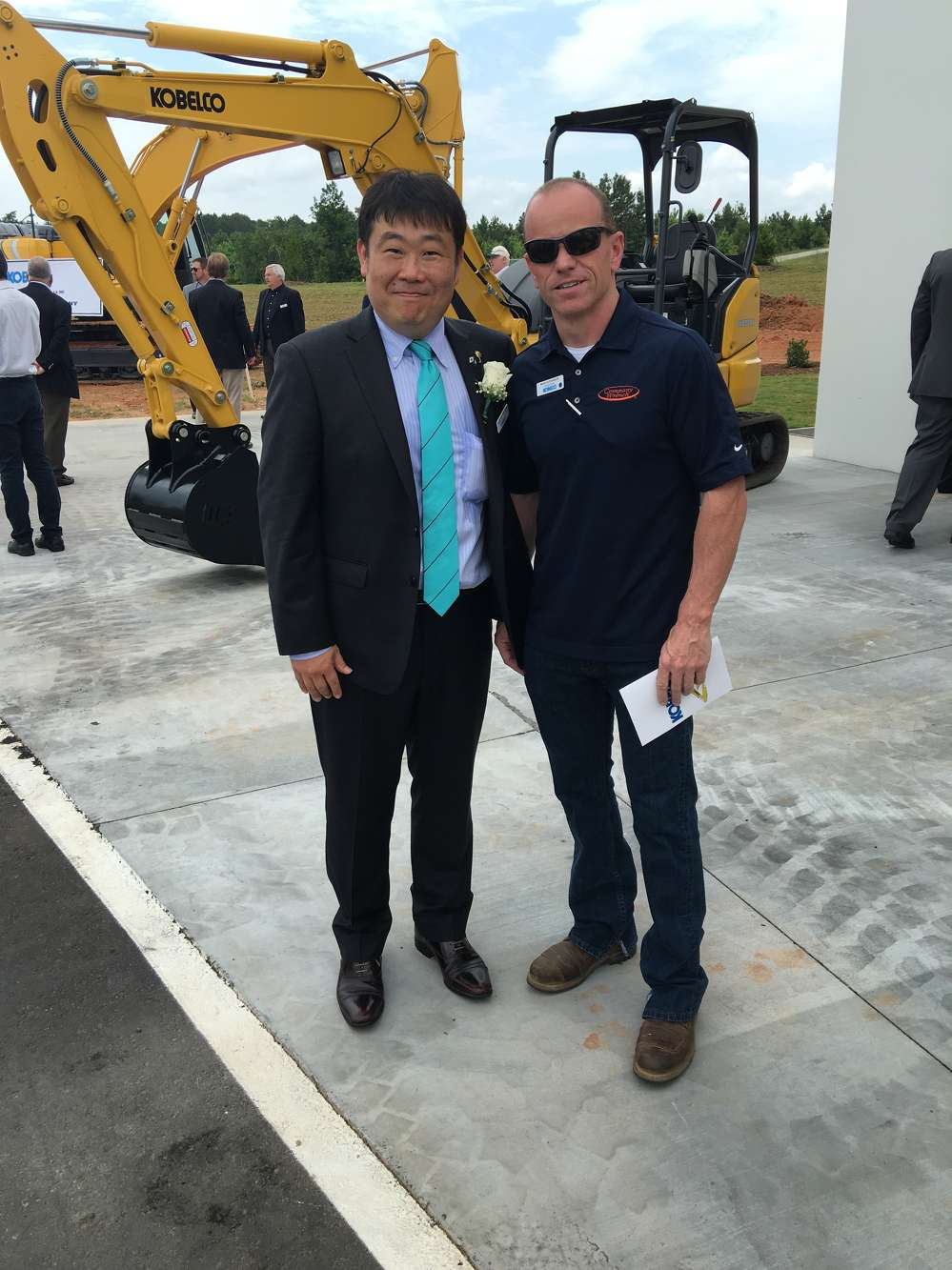 Pete Morita (L), president and CEO Kobelco Construction Machinery USA Inc., catches up with Brad Hutchinson, president of Company Wrench.