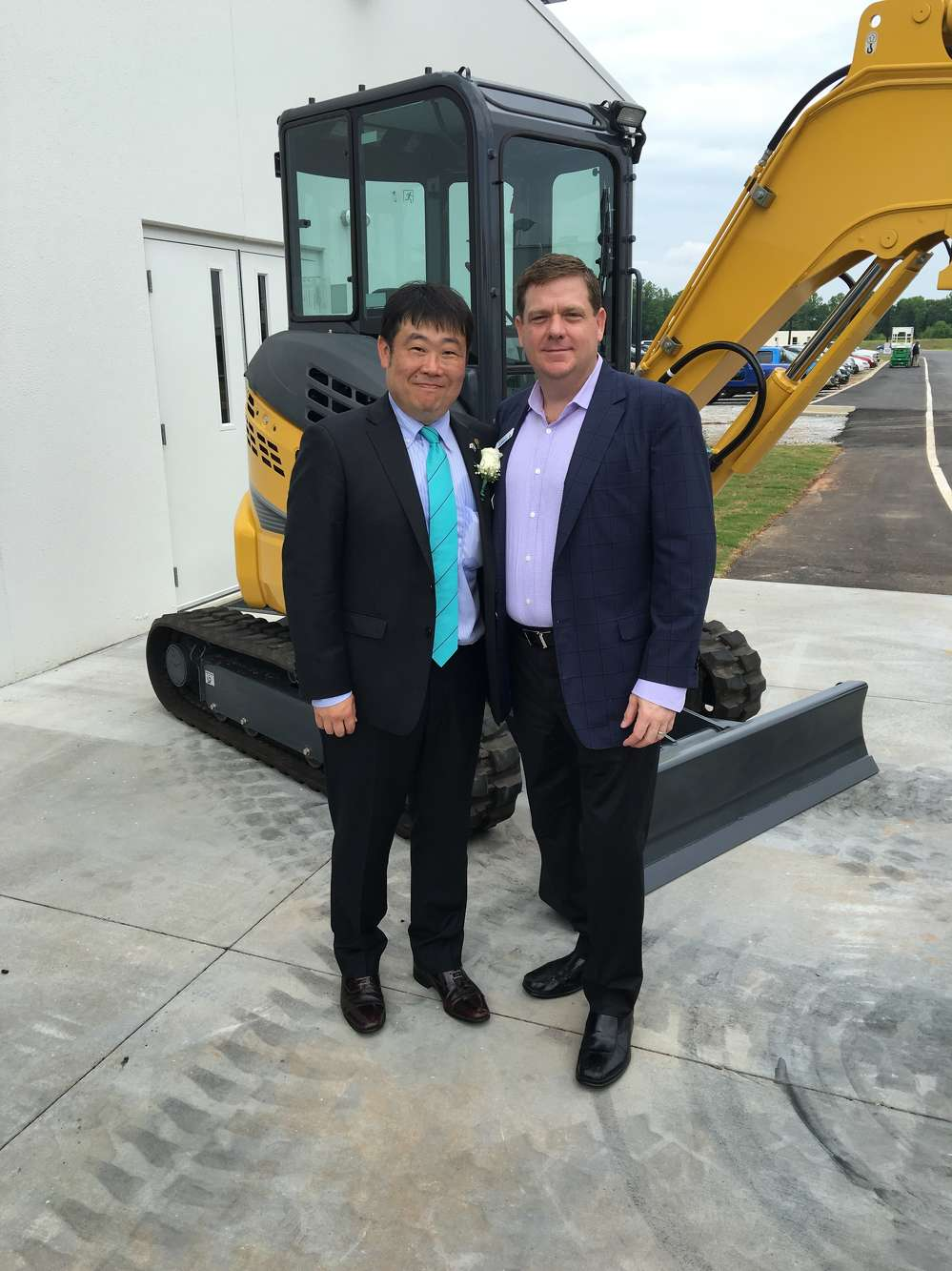 Pete Morita (L), president and CEO Kobelco Construction Machinery USA Inc., and Thomas Reynolds, president Highway Equipment Company stand in front of the Kobelco SK35SR excavator.