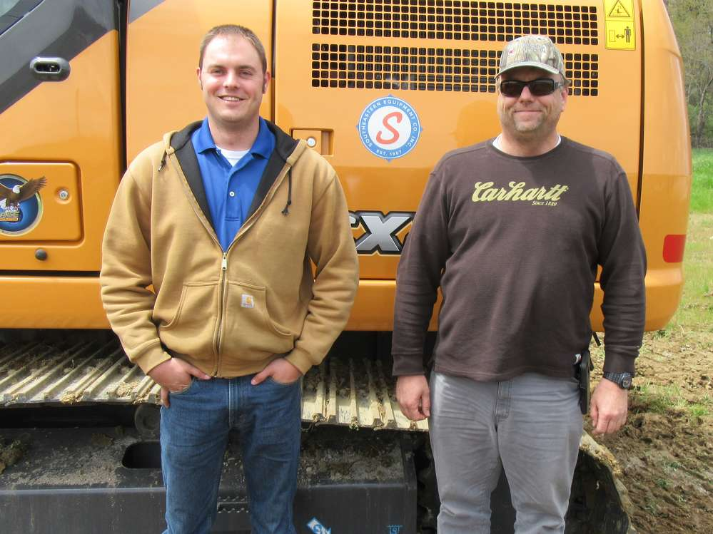 Chris Morgan (L) of Southeast Equipment Company talks with Kirk Scheid of Sheid Enterprises about this Case excavator equipped with the UBEXi  iDig wireless bucket position indicator.