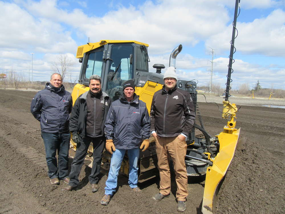 (L-R): Dan Hendriks, GeoShack vice president and regional manager; Dave Pytlowany; Chris Farnsworth, GeoShack; and Karl Doppelberger, AIS Construction Equipment Corporation; stand ready to field questions about this John Deere 650K dozer equipped with Topcon's 3DMC2 system.