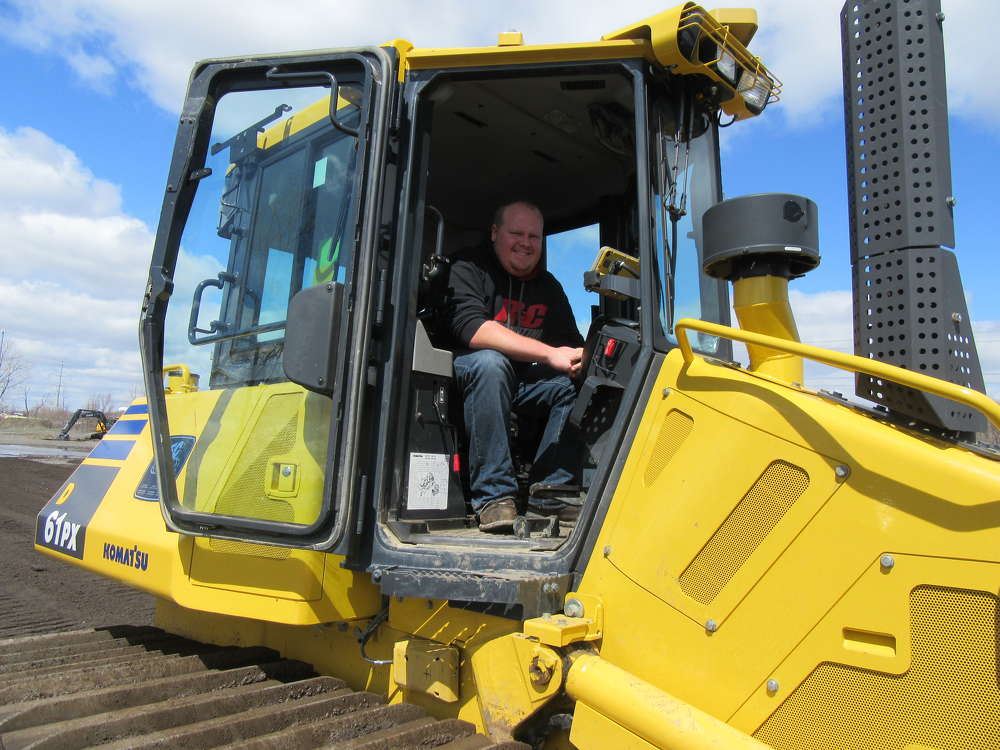 Ryan Hitchcock of R&C Excavating, Webberville, Mich., tries out a Komatsu 61PX dozer equipped with Topcon's new 3D-MCMAX mast free system.