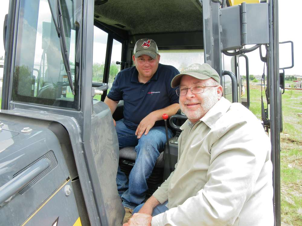 In Columbus, Ohio, Nick Baker (L) of GeoShack speaks with Dwight Tillis of P&L Systems about this John Deere 850K equipped with a Topcon 3DMC2 system.