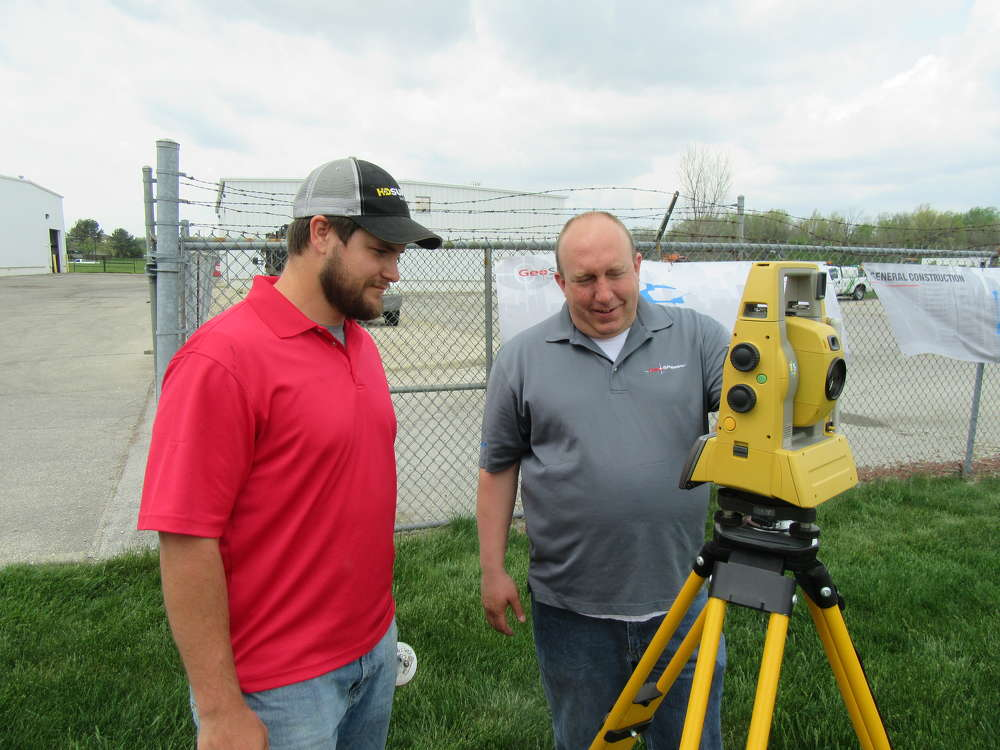 Justin Buenger (L) of Connie Construction talks to Paul Naylor, GeoShack, about Topcon's PS Series Robotic Total Station.