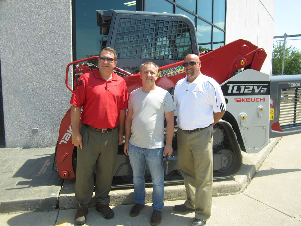 Robert Kuznair (C) of RCC Commercial Construction looks at this Takeuchi TL12V 2 and asks Jeff Vodnik (L) and Paul Wade, both of Takeuchi, about the machine.