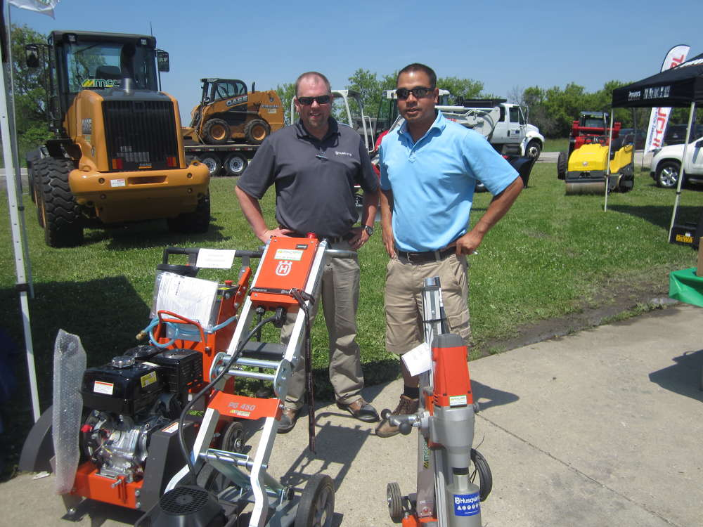 Brian Bollinger (L), Husqvarna Construction Products, explains the features of the Husqvarna product lineup to Sam Kukadia, Material Solutions Laboratory.