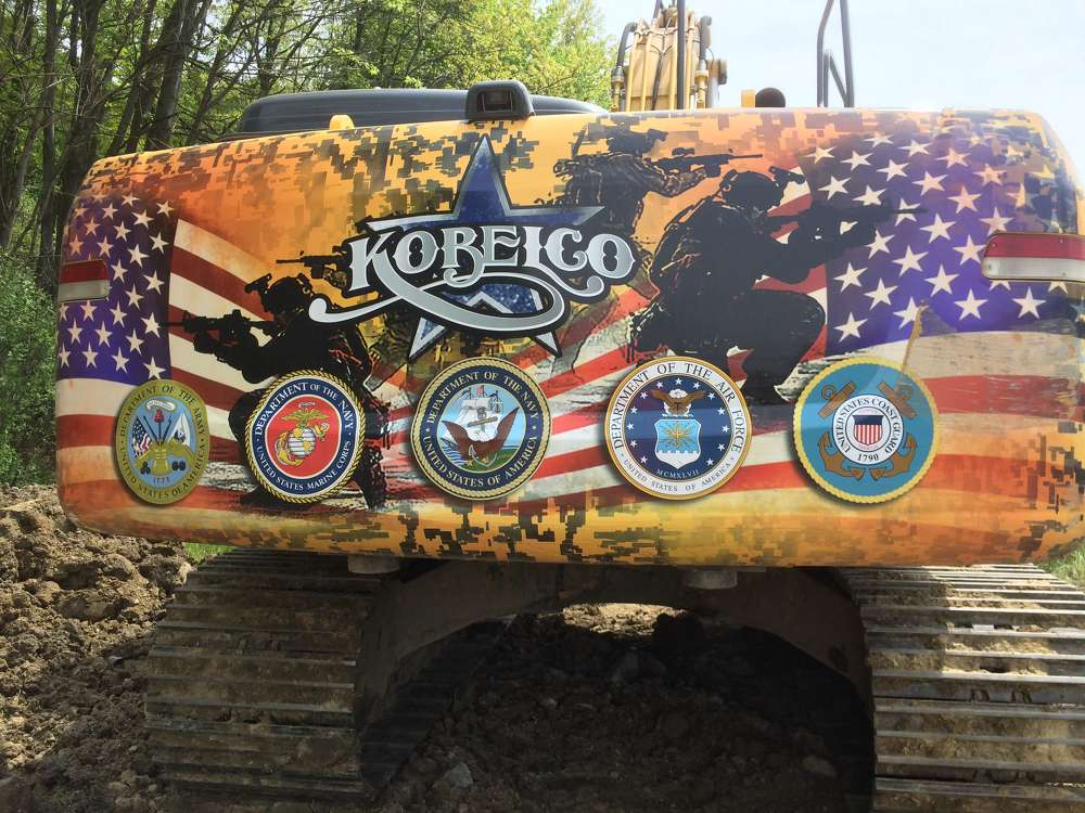 A Kobelco 330 excavator features logos of the Wounded Warrior Project, which helps Iraq and Afghanistan war veterans from the Marines, Army, Air Force and Navy. Some of these excavators have been featured in parades to raise funds for the program and create awareness of the problems facing returning veterans.