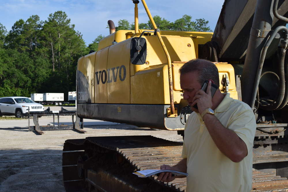 Robby Udelson, president of PowerTrac Machinery in Miami, Fla., takes a close look at some of the excavators.