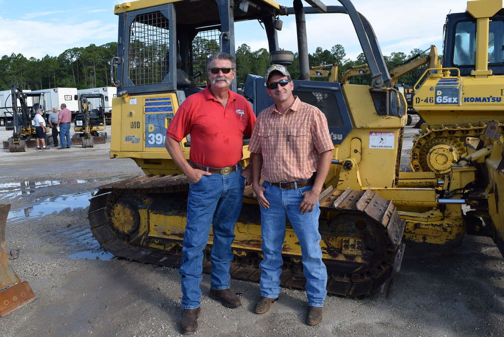 Jim Lawrence (L) of Jim Lawrence Trucking talks with Dwight Mast of North Florida Equipment Rental about buying a dozer.