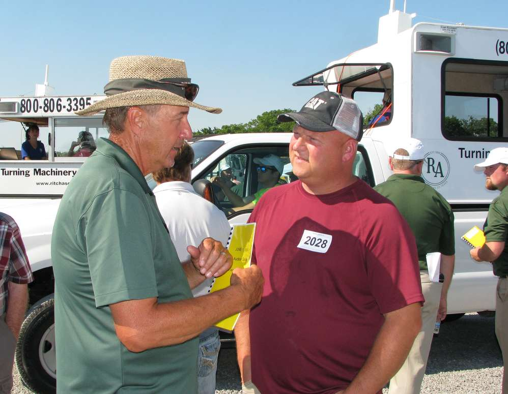 As the trucks roll out to start the auction, Ritchason Auctioneers' Dewain Ritchason (L) talks with one of his regular customers, Brad Higgins of Dirtworks Unlimited, Chattanooga, Tenn.