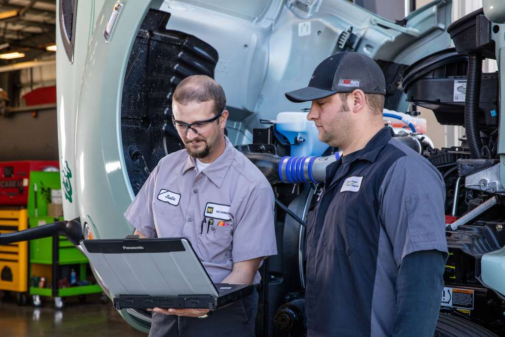 Justin MacDonald (L), a mechanic with Papé Kenworth — Redmond, goes over the service schedule for Central Oregon Truck Company's Kenworth T680 with COTC maintenance shop foreman Travis Seeger.
