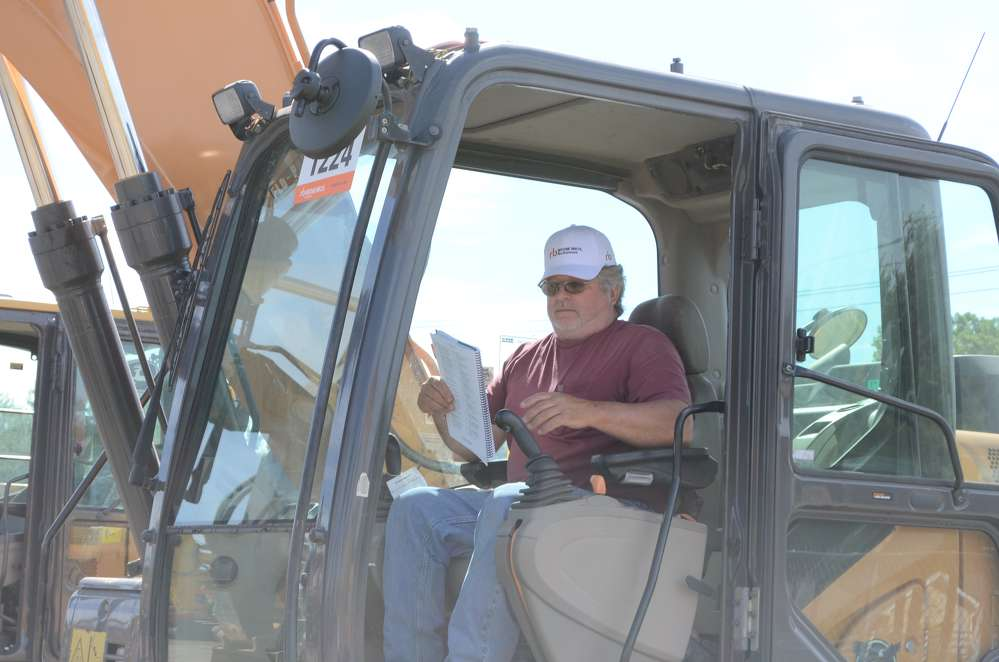 Gerard Dumsha of Go Away Acres Farm in Princess Ann, Md., checks out the controls on this excavator.