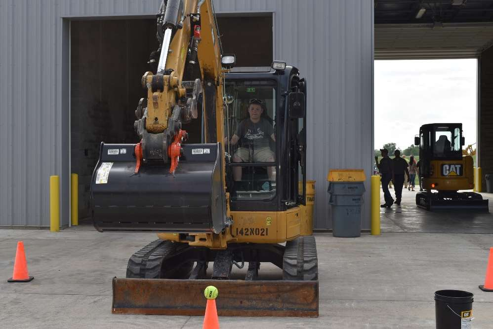 An attendee shows off his operating skills on the excavator tennis ball chal