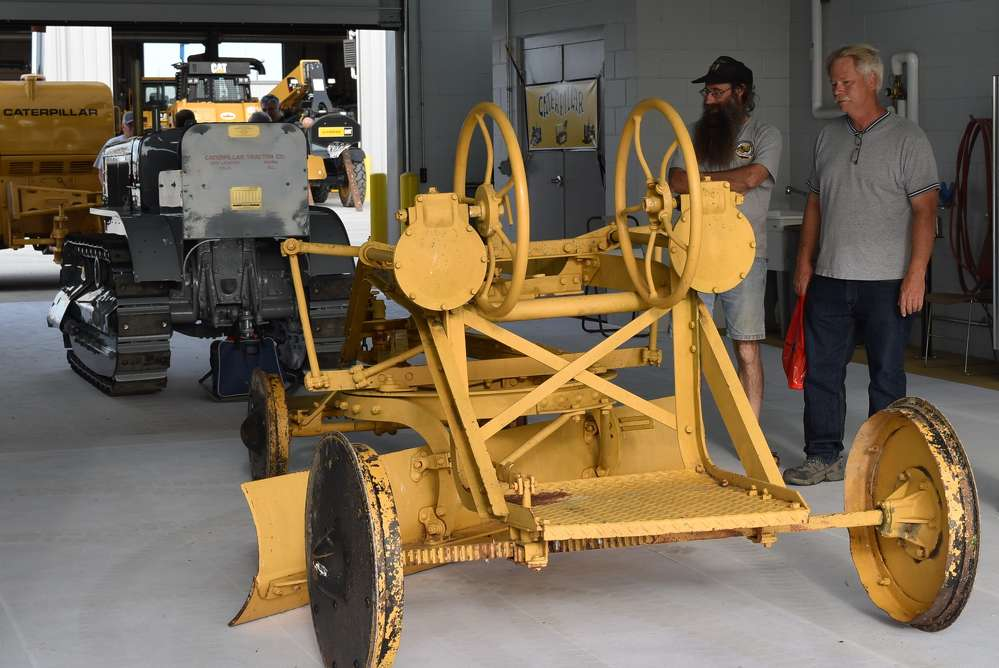 Attendees check out the antique tractors displayed by the Antique Caterpillar Machinery Owners Club.