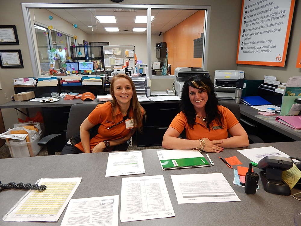 Rachel Olson (L) and Genea Rissell, administrative assistants of Ritchie Bros., greet customers