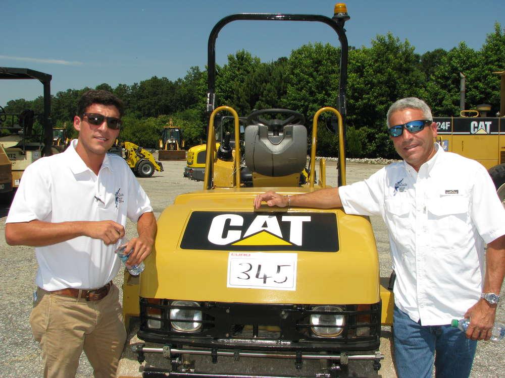 Ben Fernandez (L), BenZach Contractors, Marietta, Ga., and Raul Fernandez, Zacscabe Farms, Butler, Ga., look over some of the compactors in the sale lineup.