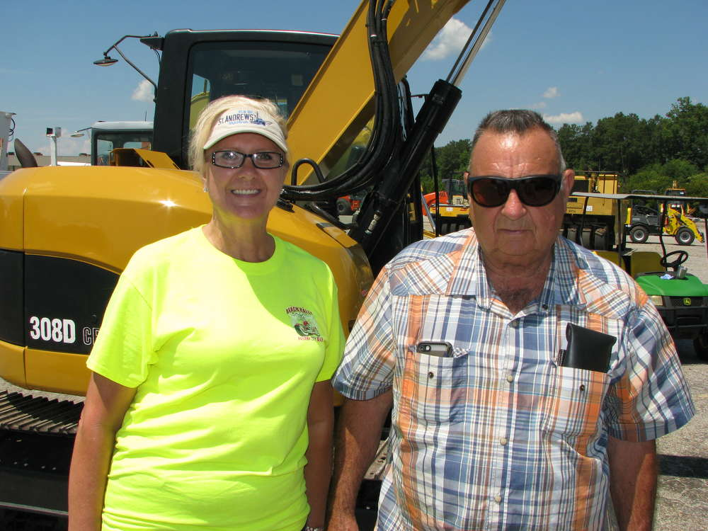 Cindy Baxter (L) and H.C. Hare, both of 157 Hardware, Cullman, Ala., shop the inventory of the mid-sized excavators about to roll across the auction ramp.
