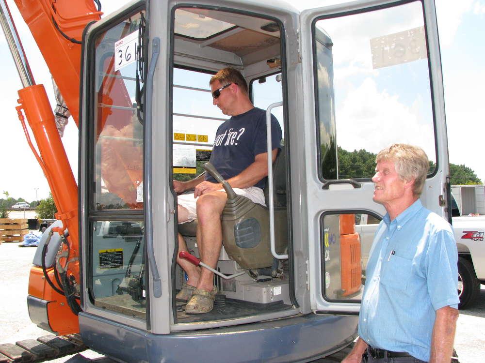 Kevin Roberts (L) and Jesse Roberts, Fairburn, Ga., look over a Hitachi EX75UR.