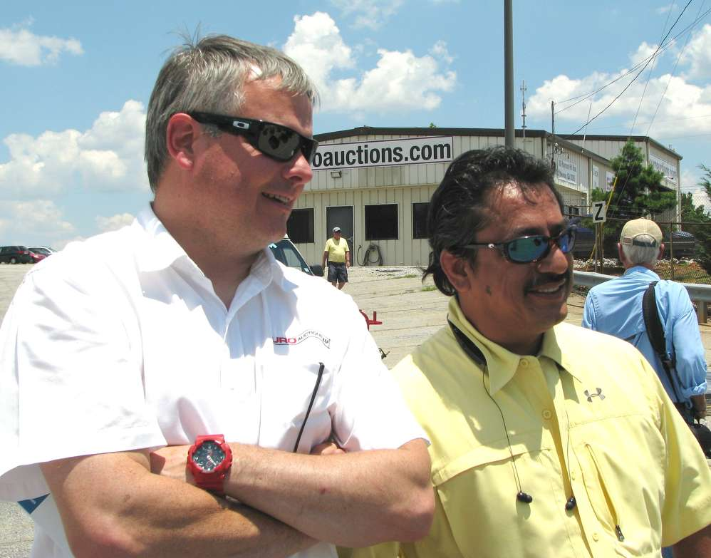 David Betts (L) of Euro Auctions U.S.A. and Jesus Ramirez of Vesco Tractors, Gadsden, Ala., watch the bidding.