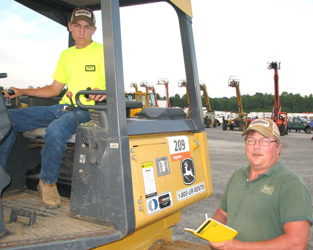 Craig Zoellner Jr. (L) and Craig Zoellner, both of Piedmont Paving, Newnan, Ga., look over the selection of dozers in the sale.