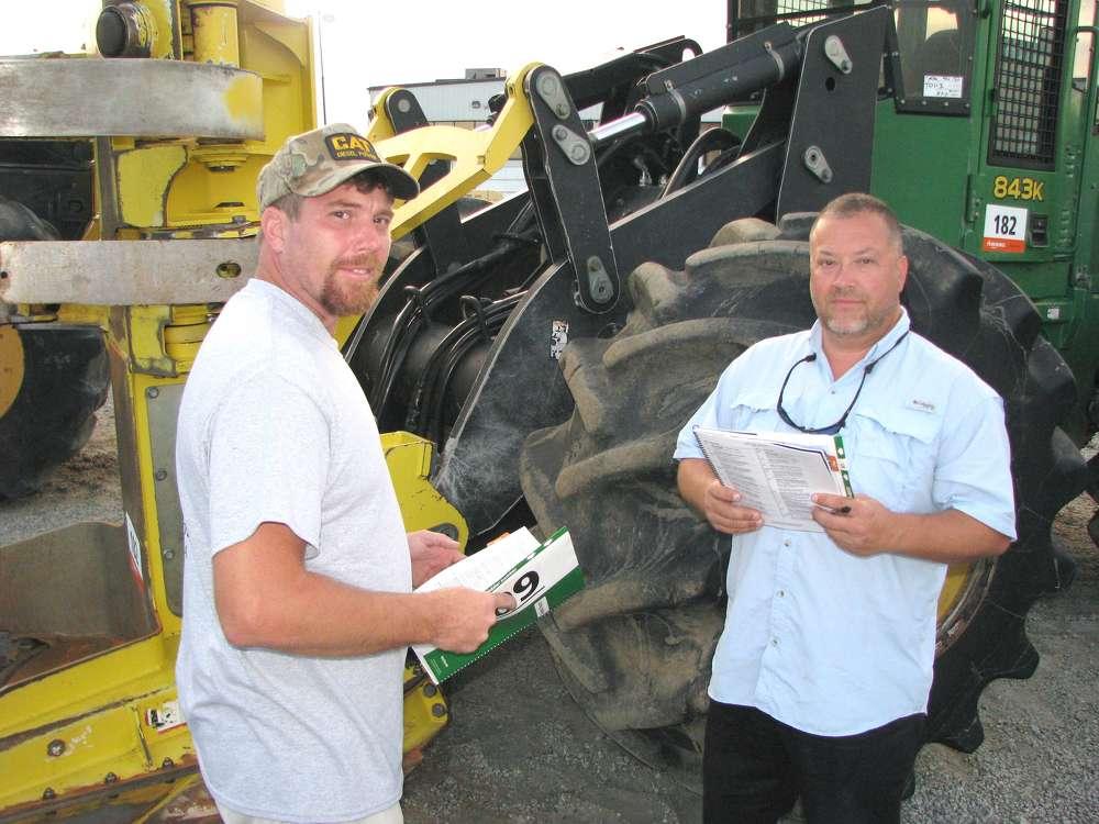 Johnny Bateman (L), Bateman Forest Products, Gay, Ga., and Keith Reems of Lanier Equipment, Lula, Ga., look over a late-model John Deere 843K feller buncher.
