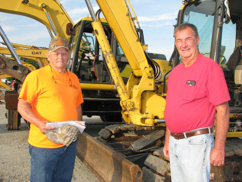 Vernon Dorminey (L) and Gary Loudermilk, both farmers based in Carnesville, Ga., look for a bargain on a mid-sized dozer.