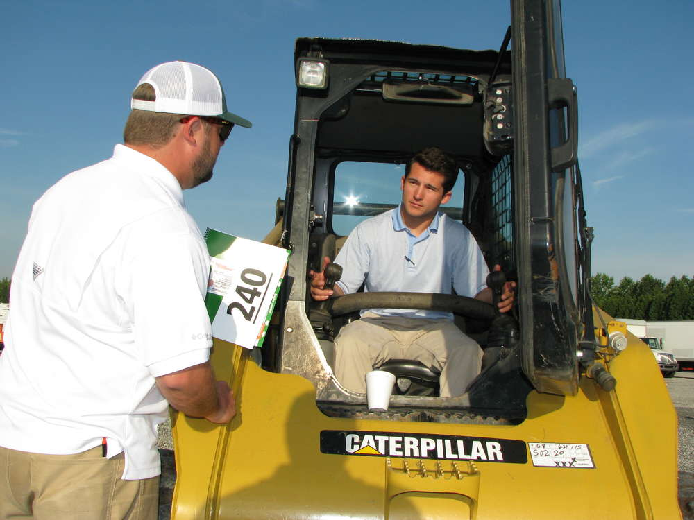 Zac Shepherd (L) and Dustin Underwood of SHP Mine Group, Alpharetta, Ga., are interested in this Cat 252B skid steer loader.