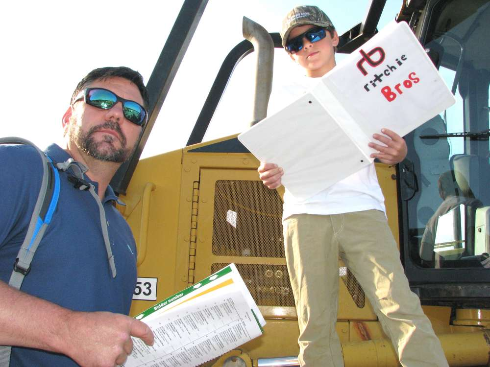 Nine-year-old Caden Morehead stayed up later than his dad, James of Complete Demolition Services, Carrollton, Ga., researching machines and compiling his own binder of information for the Ritchie Bros. sale.