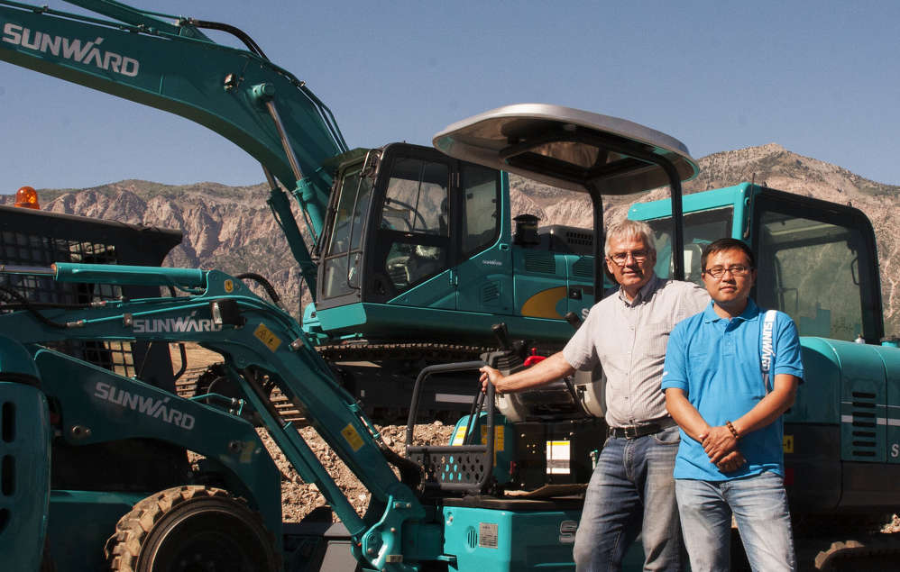 Rob Gibb (L), president and founder of Pacific Tri-Star, and Jun Wang, director of Sunward N.A., stand in the equipment yard in Farr West, Utah.