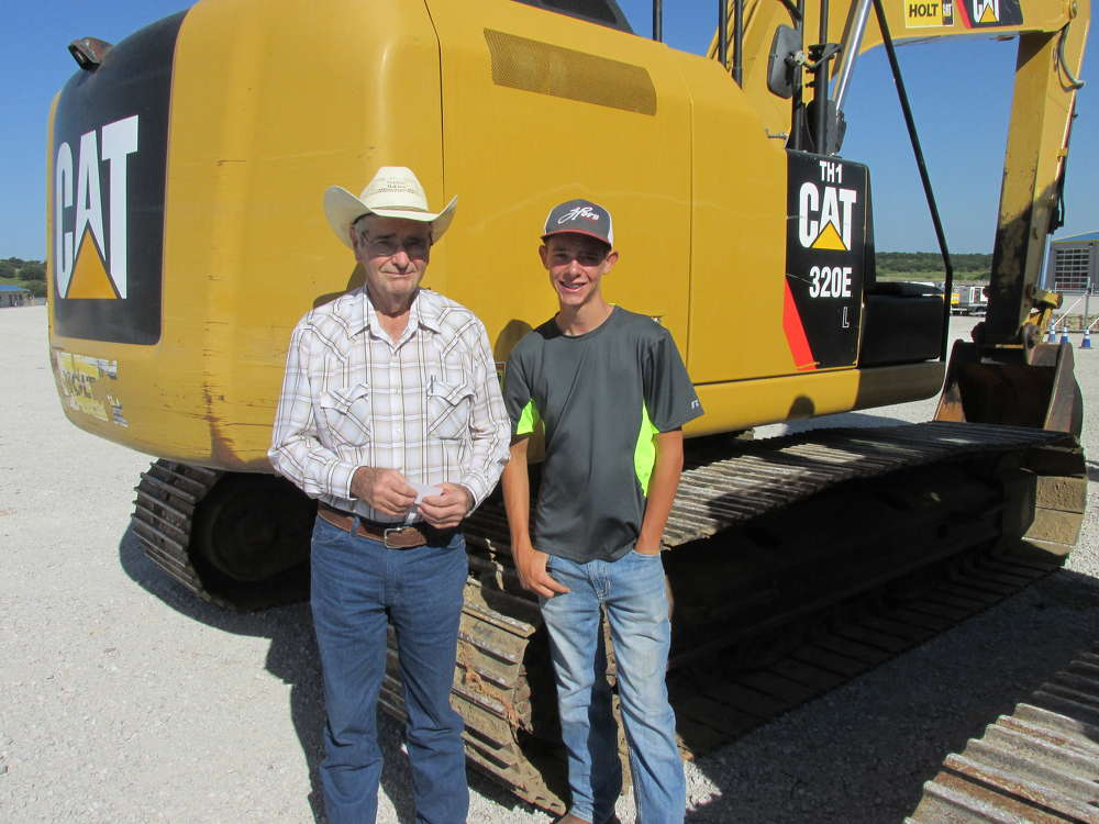 Thomas Holland (L) and his grandson, J.T., of Holland Dozers, Moran, Texas, have put this Cat 320E through its paces.