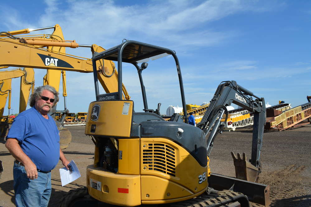 Dave Bauch of SRC Enterprises, an excavating contractor in Colorado, inspects a John Deere 35D mini-excavator.