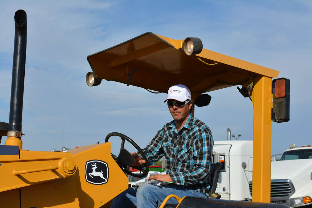 Paul Spencer of ATC in Bluewater, N.M., puts a John Deere 210 LE through its paces.