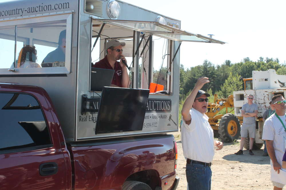 Auctioneer Matt Hostetter calls bids from inside the North Country Auctions mobile truck.