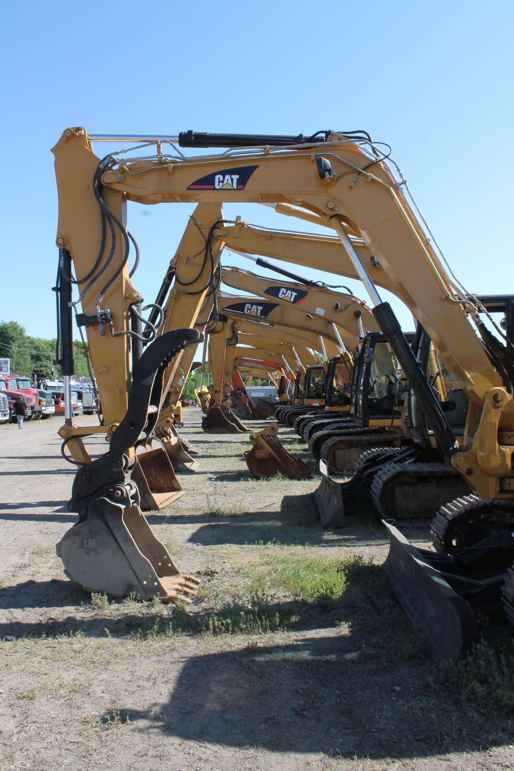 Excavators are lined up, waiting for buyers.