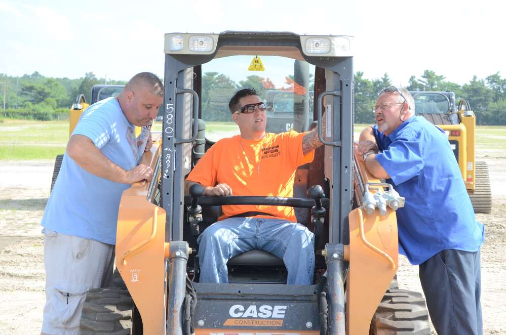 (L-R): Pete Fengen of P Denson Equipment, Little Ferry, N.J.; Ken Christensen, owner of Christensen Recycling, and his father, both of Sayreville, N.J., appear to be very interested in this Case skid steer.