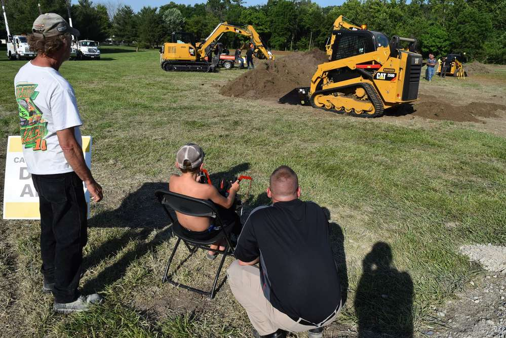 Jason Ross (R), Altorfer condition monitoring specialist, helps attendees demo the new RemoteTask remote control system for Cat D Series skid steer, multi-terrain and compact track loaders.