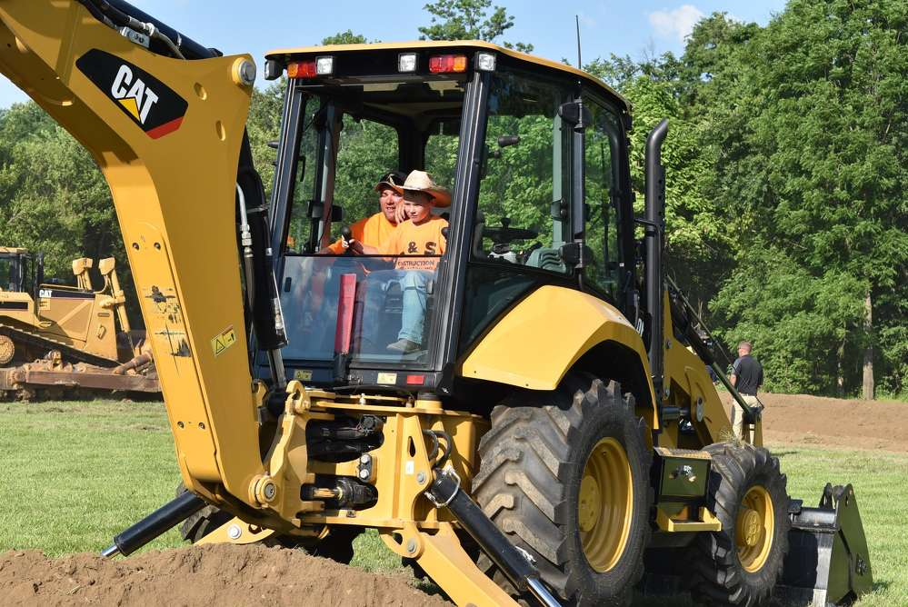 Kolton Semkin (R) demos a Cat backhoe loader with his uncle, Levi Muehrin. Kolton is the son of Nick Semkin, Altorfer field technician, and his wife Heather Semkin.