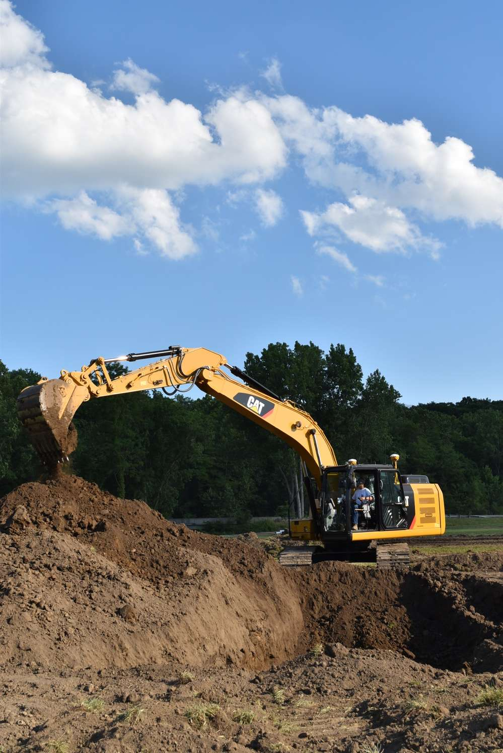 An attendee demos a 323FL hydraulic excavator with grade assist.