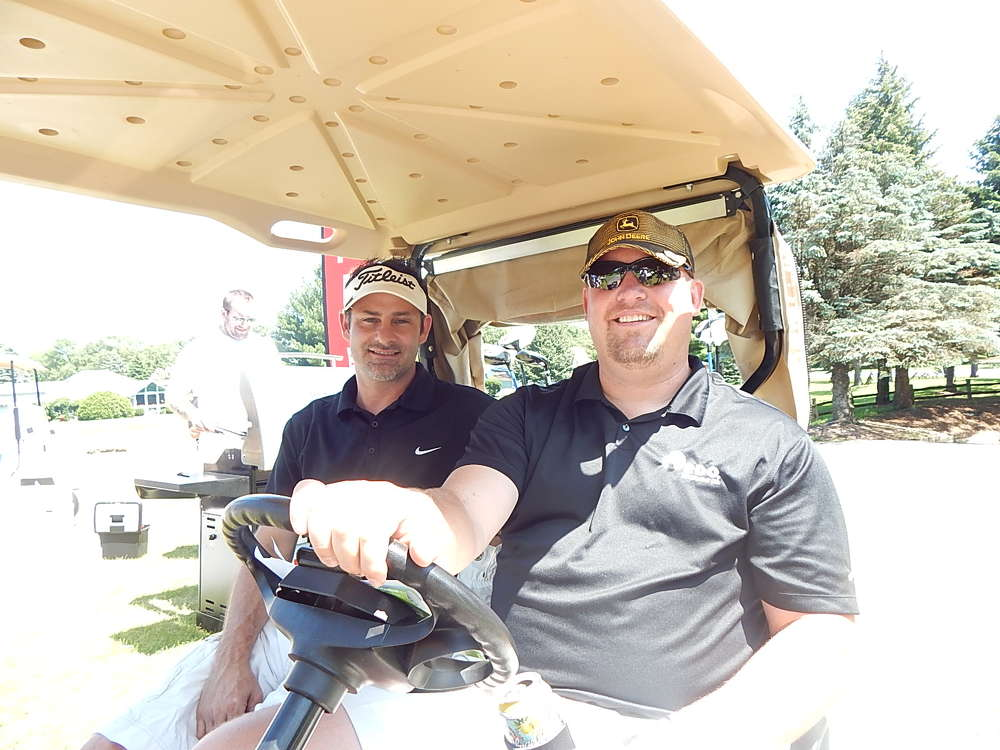 Keith Yetzer (L), president of YTS Tree Care Experts, Rogers, Minn., and Scott Weness, sales manager of RDO Equipment Co., take a ride on the course.