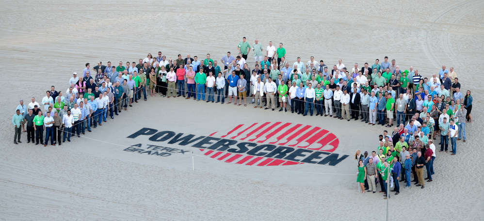 "Powerscreen hosted a world dealer conference in Florida in 2014. A selection of dealers and customers from around the world who attended flank the ""brand in the sand."""