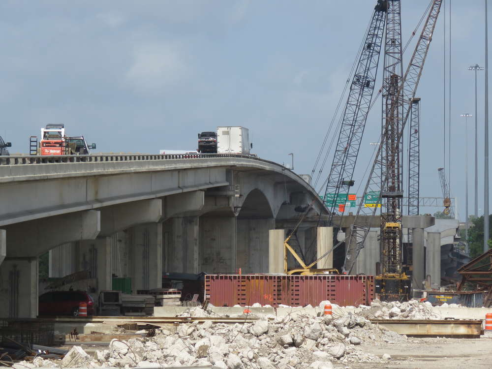 TxDOT photo. Current work on the Purple Heart Memorial Bridge includes driving pile on the westbound section and installing bridge deck panels and overhang brackets on span 1 of the bridge.