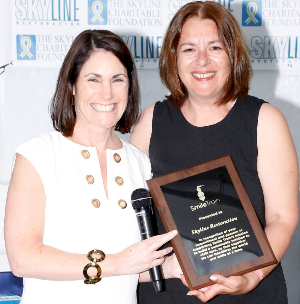 (L-R) Smile Train CEO Susannah Schaefer presents congratulatory plaque to Eva Hatzaki, Skyline Restoration Director of Marketing, at Skyline's Eighth Annual Golf Classic which has raised close to 400K for Smile Train since 2009. Credit: George Constantinou Photography.