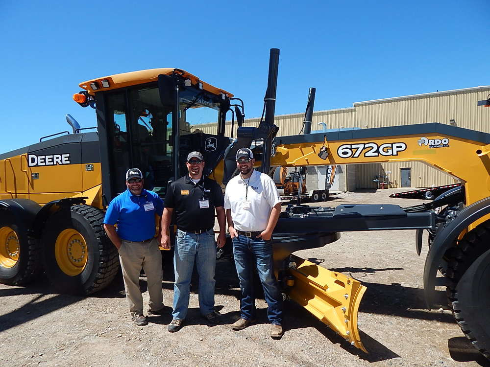 (L-R): Chris Mullen, sales; Scott Weness, sales manager; and Ryan Miller, sales, all of RDO's Burnsville, Minn. location, stand with a new John Deere 672 GP 255 hp motorgrader.