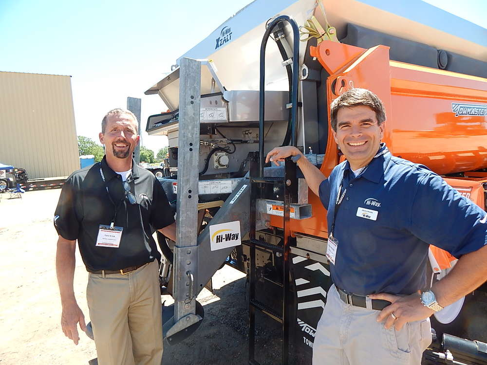 Marty Wolske (L), director of business development, and Tom Krick, regional sales manager of High-Way Equipment Company, Cedar Rapids, Iowa, in front of a XZALT Precision sand and salt applicator system.