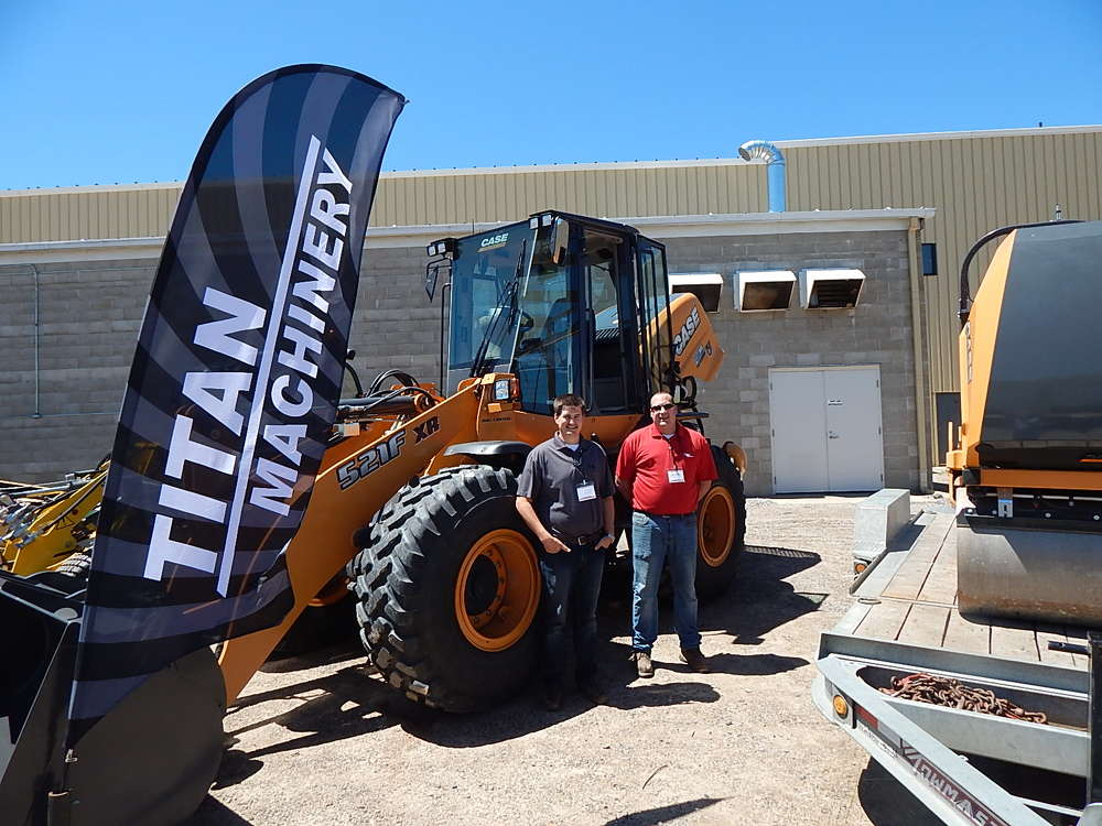Brenden Honebrink, business manager, Titan Machinery, and Todd Widmer, field marketer,  Titan Machinery, Shakopee, Minn., display the Case 521F XR wheel loader and a Case DV23 roller.