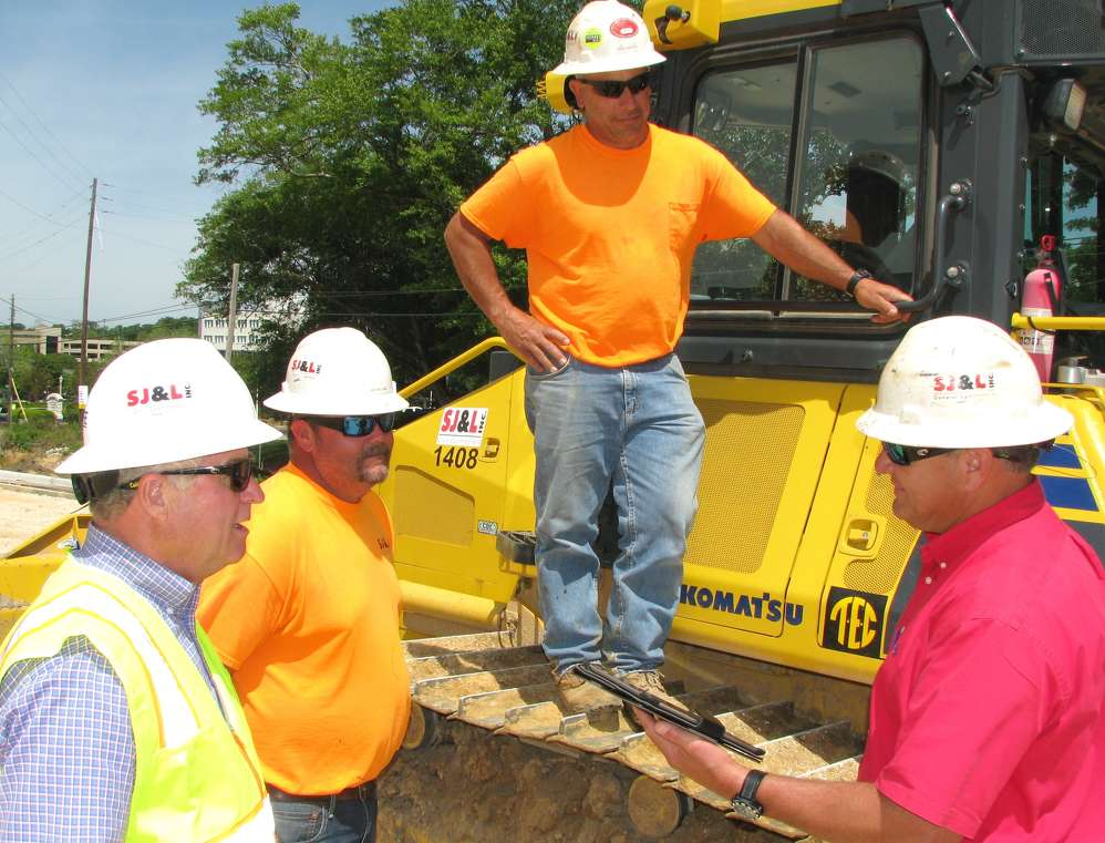 (L-R): Michael Tew, Wes Williams and Chris Cincotta, all of SJ&L, discuss the productivity of the Komatsu machines on the job site with Chris Howard of Tractor & Equipment Company.