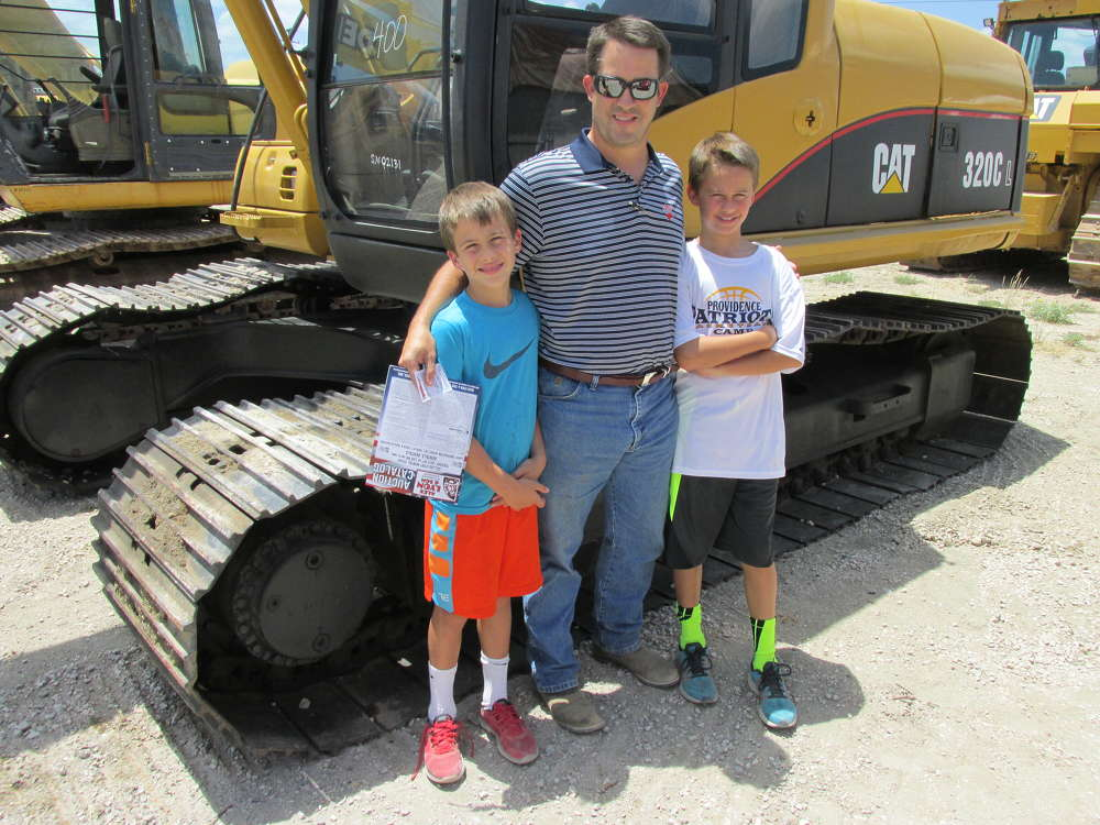 Grant Dixon (C), Providence Equipment of Athens, Texas, and his two sons, Mac (L) and Mitchell, were looking over this Cat 320C excavator.