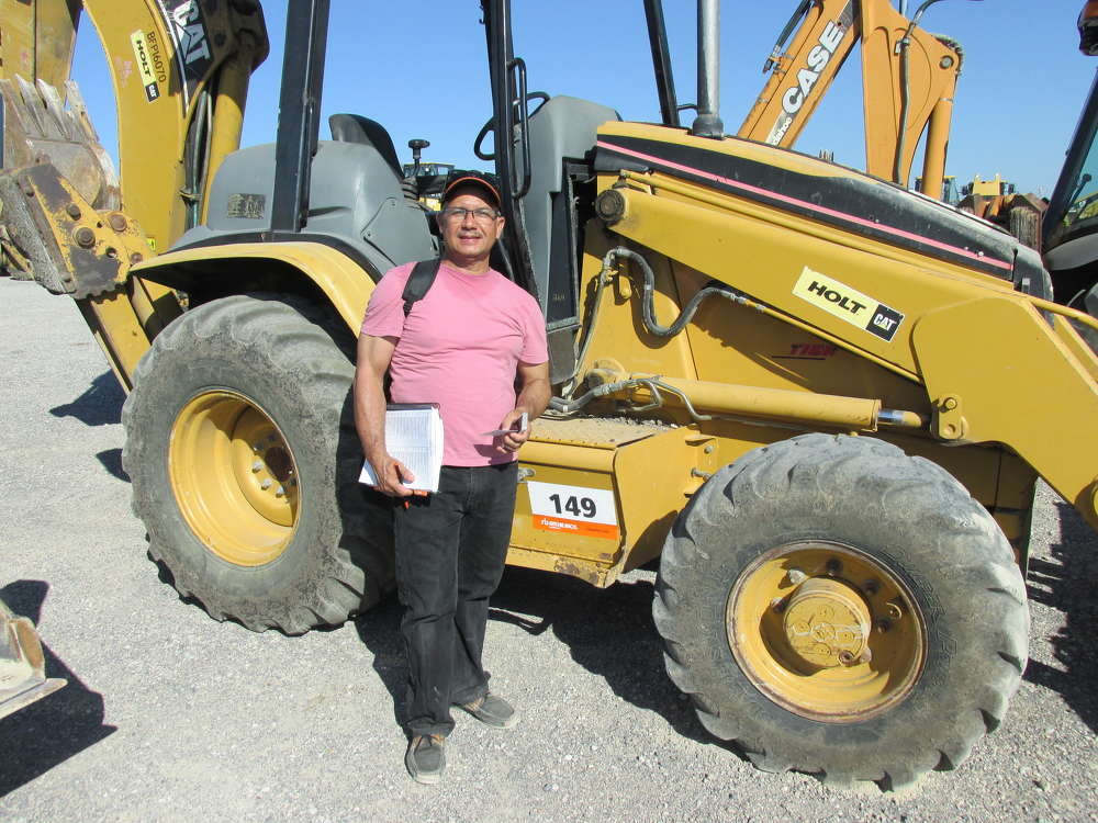 Miguel Olivo of Service Equipment Depot in Orlando, Fla., takes a close look at this Cat 416D loader/backhoe.