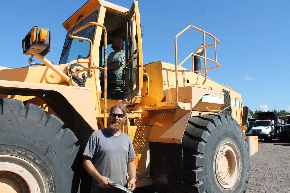 Dan Northcott sits behind the wheel of this Dressta wheel loader, while his brother, Ben, looks at the specs. They are co-owners of Fuzzy Brothers Excavation of Walpole, N.H.